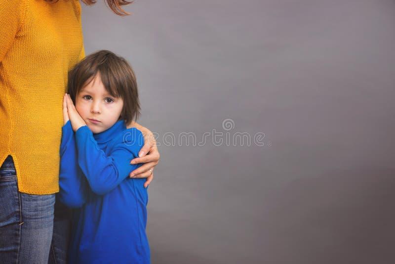 Droevig isoleerde weinig kind, jongen, die zijn moeder koesteren thuis, imag royalty-vrije stock fotografie