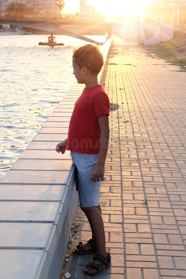 Droevig jongensportret op dijk backlit, gestemd beeld royalty-vrije stock foto