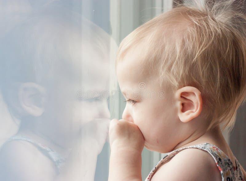 Droevig kind die uit het venster kijken stock fotografie