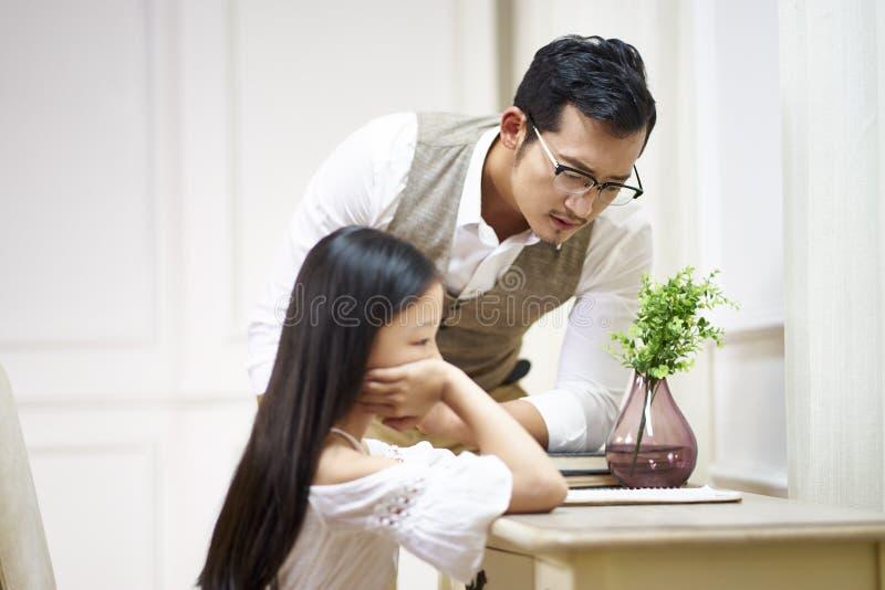 Droevig krijgt weinig Aziatisch meisje comfort van vader stock foto