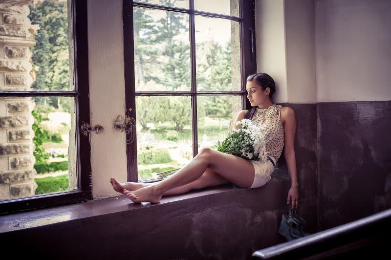 Droevig meisje dichtbij een venster royalty-vrije stock foto's