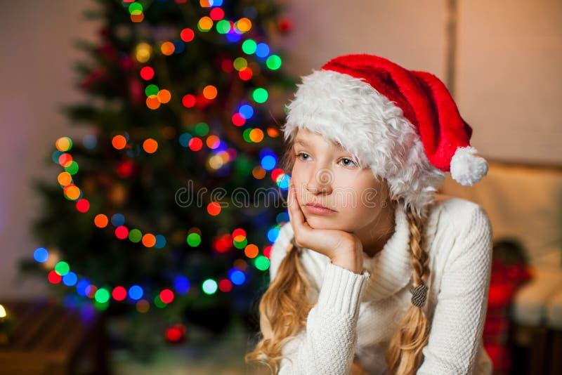 Droevig meisje dichtbij Kerstmisboom thuis royalty-vrije stock foto's