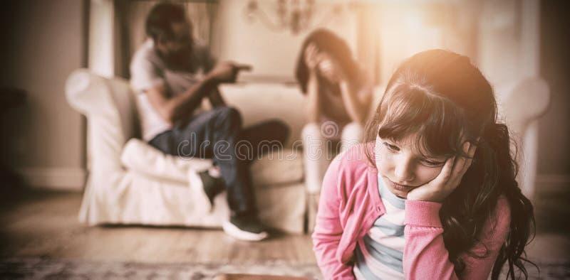 Droevig meisje die aan haar ouders het debatteren luisteren royalty-vrije stock fotografie