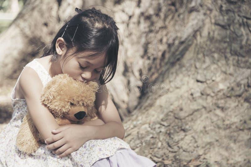 Droevig meisje die alleen in het park voelen Eenzame concepten Mooi peutermeisje en pluizig verblijf alleen onder de grote boom stock foto