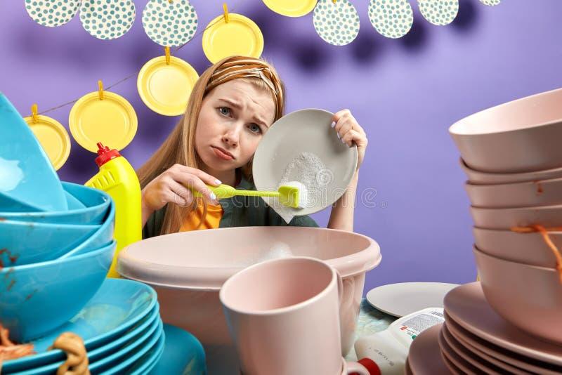 Droevig meisje die feds omhoog en in de keuken met blauwe muur schoonmaken wassen stock foto