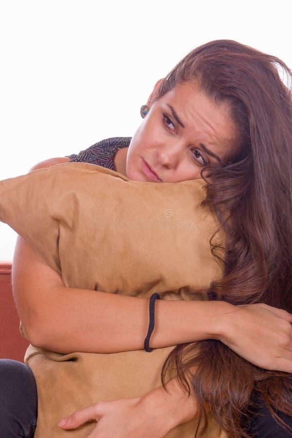 Droevig meisje die hoofdkussen koesteren stock foto's