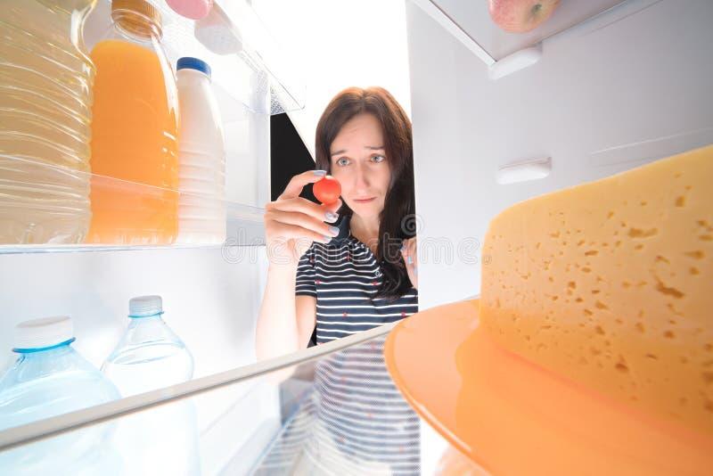 Droevig meisje die koelkast onderzoeken en enige tomaten in haar houden royalty-vrije stock foto's