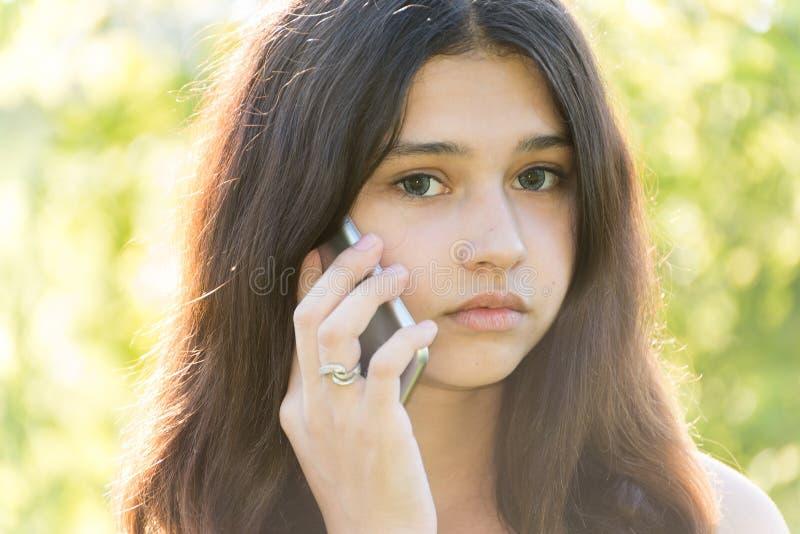 Droevig meisje die op telefoon in park spreken stock afbeeldingen