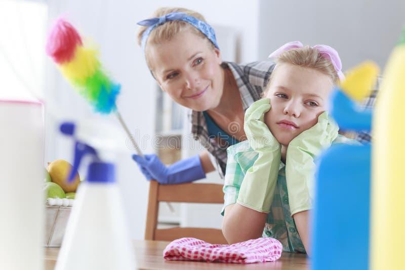 Droevig meisje en haar mamma het schoonmaken stock afbeelding