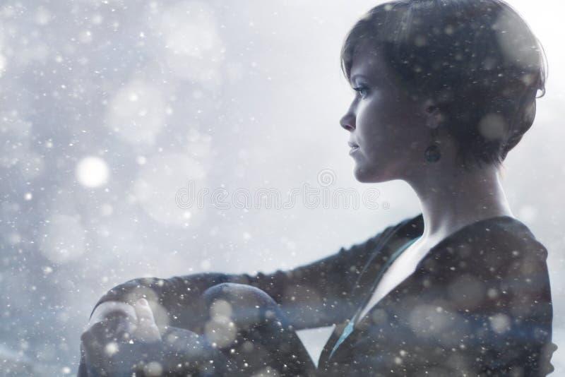 Droevig meisje op de vensterbank die uit venster kijken stock afbeeldingen