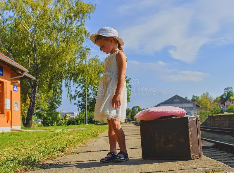 Droevig meisje op een station, die op de trein met uitstekende koffer wachten Eenzaam en ongelukkig concept royalty-vrije stock afbeelding