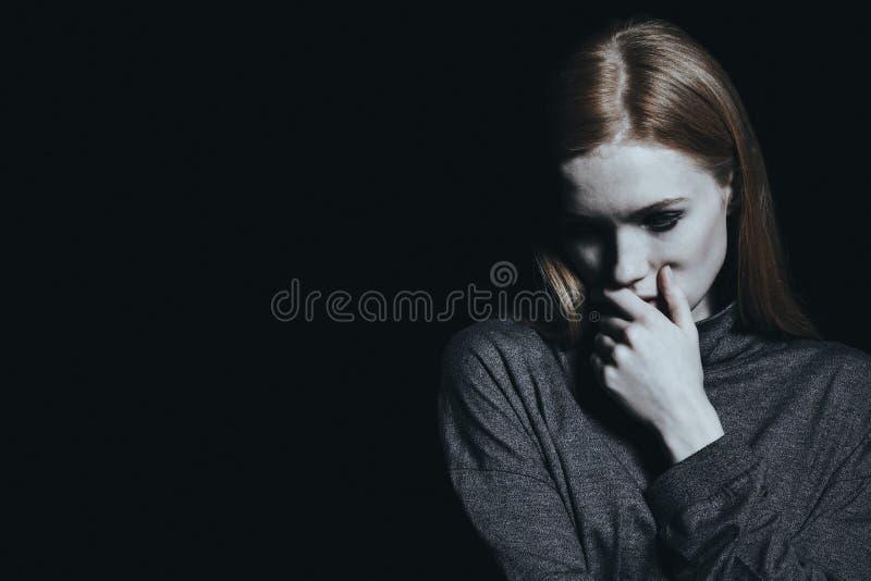 Droevig meisje tegen zwarte muur stock afbeelding