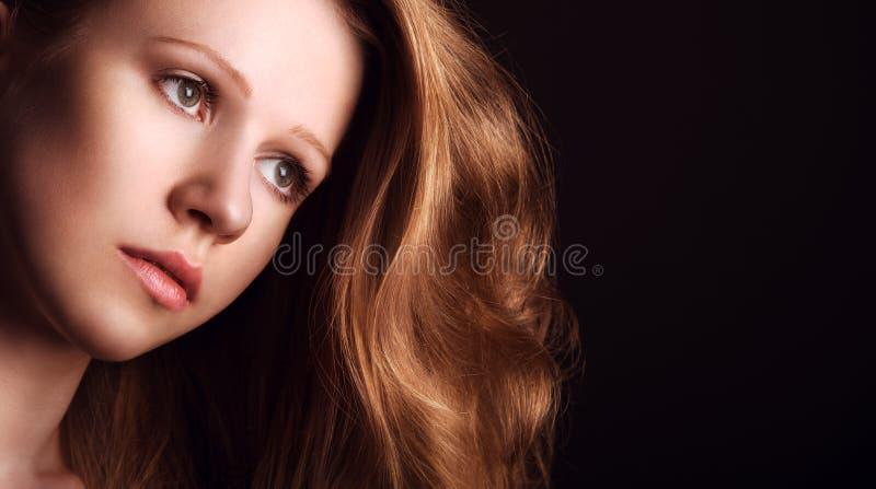 Droevig, melancholisch meisje met lang rood haar op een donkere achtergrond stock afbeeldingen