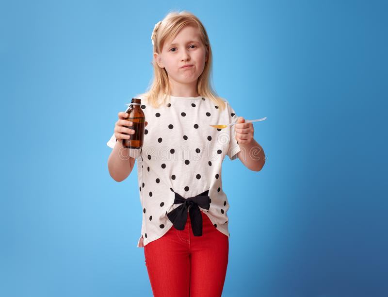 Droevig modern meisje die lepel van de opschorting van kinderen op blauw nemen royalty-vrije stock foto's