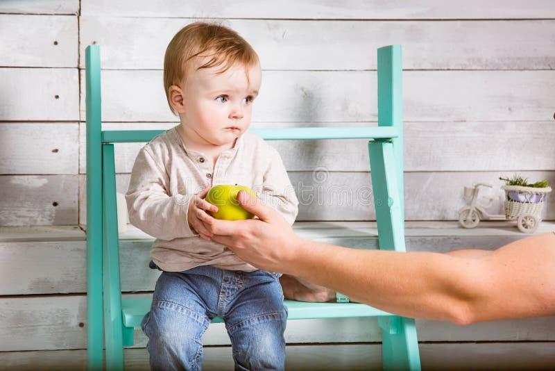 Droevig neemt weinig babyjongen een appel van vader Hij zit op de stappen binnen Witte Houten Achtergrond stock foto