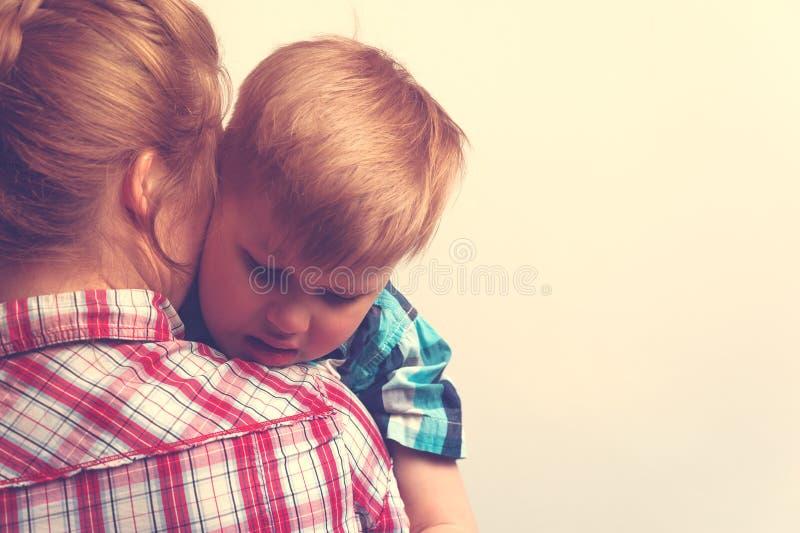 Droevig ongelukkig kind dat zijn moeder koestert stock afbeeldingen