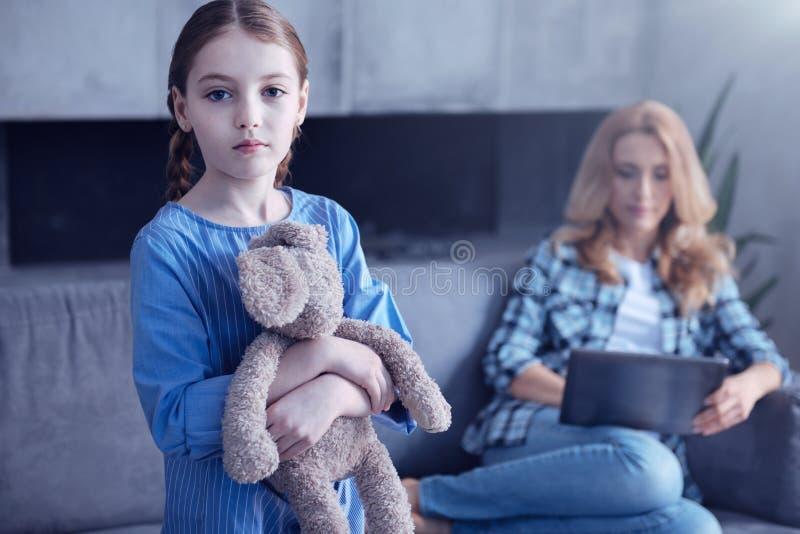 Droevig ongelukkig meisje die haar stuk speelgoed houden stock afbeeldingen
