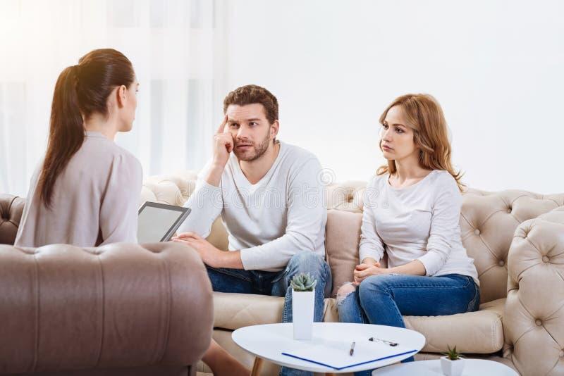 Droevig ongelukkig paar die aan de psycholoog luisteren royalty-vrije stock afbeeldingen
