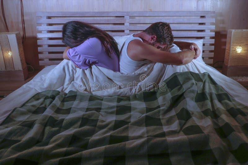 Droevig paar na binnenlandse strijd met het gedeprimeerde vrouw schreeuwen en gefrustreerde vriendzitting op bed ongelukkig in ve stock fotografie