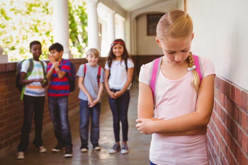 Droevig schoolmeisje met vrienden op achtergrond bij schoolgang stock afbeelding
