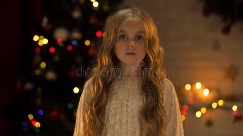 Droevig verlaten meisje die aan camera kijken die nieuwe familie in weeshuis, Kerstmistijd wachten stock afbeelding