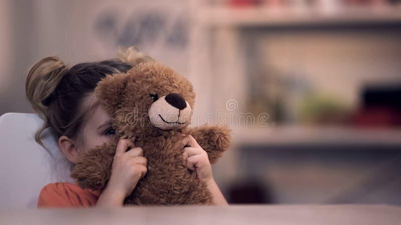Droevig vrouwelijk jong geitje die gezicht door teddybeerstuk speelgoed, familieprobleem, eenzaamheidsmisbruik behandelen royalty-vrije stock foto