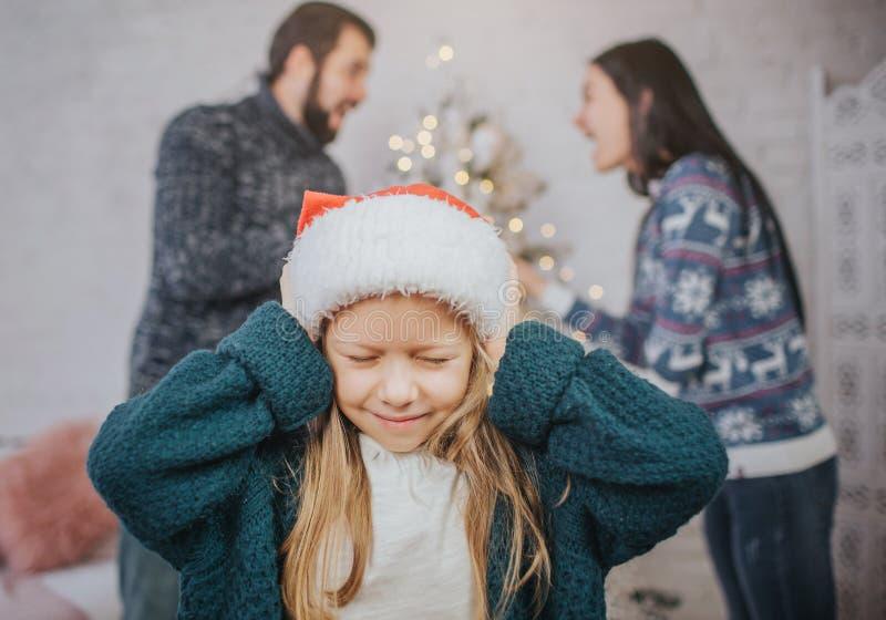 Droevig, wanhopig meisje tijdens oudersruzie Belemmer de oren Familieruzie op de vooravond van Kerstmis stock fotografie