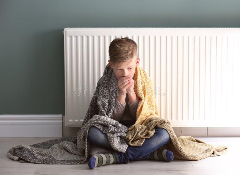 Droevig weinig jongen die aan koude op vloer lijden royalty-vrije stock foto's
