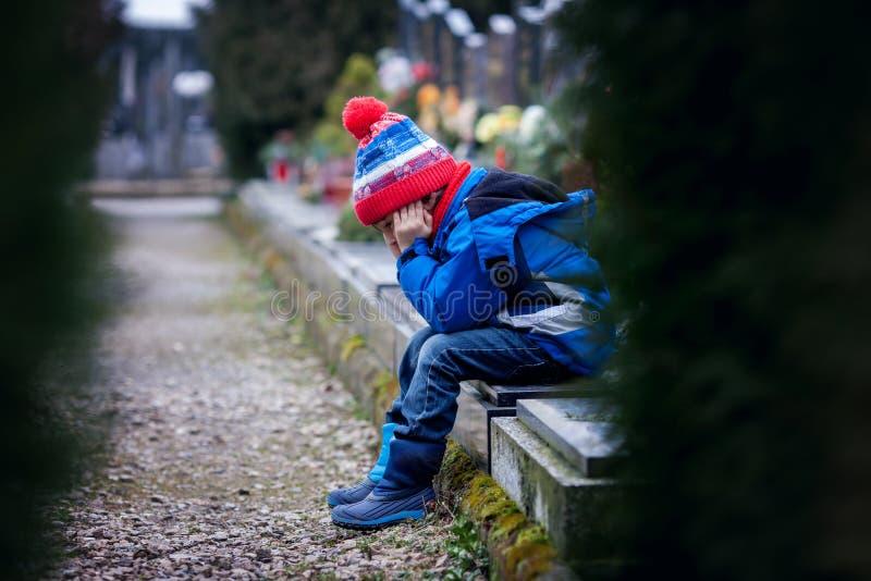 Droevig weinig jongen, die op een graf in een begraafplaats zitten royalty-vrije stock afbeeldingen