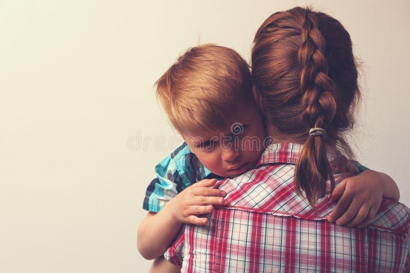 Droevig weinig jongen die zijn moeder thuis koesteren royalty-vrije stock foto's