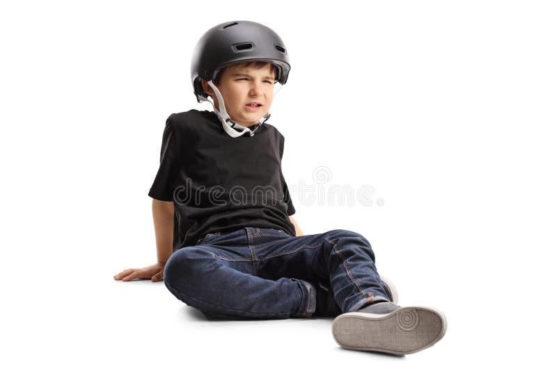 Droevig weinig jongen met helmzitting op de vloer royalty-vrije stock foto's