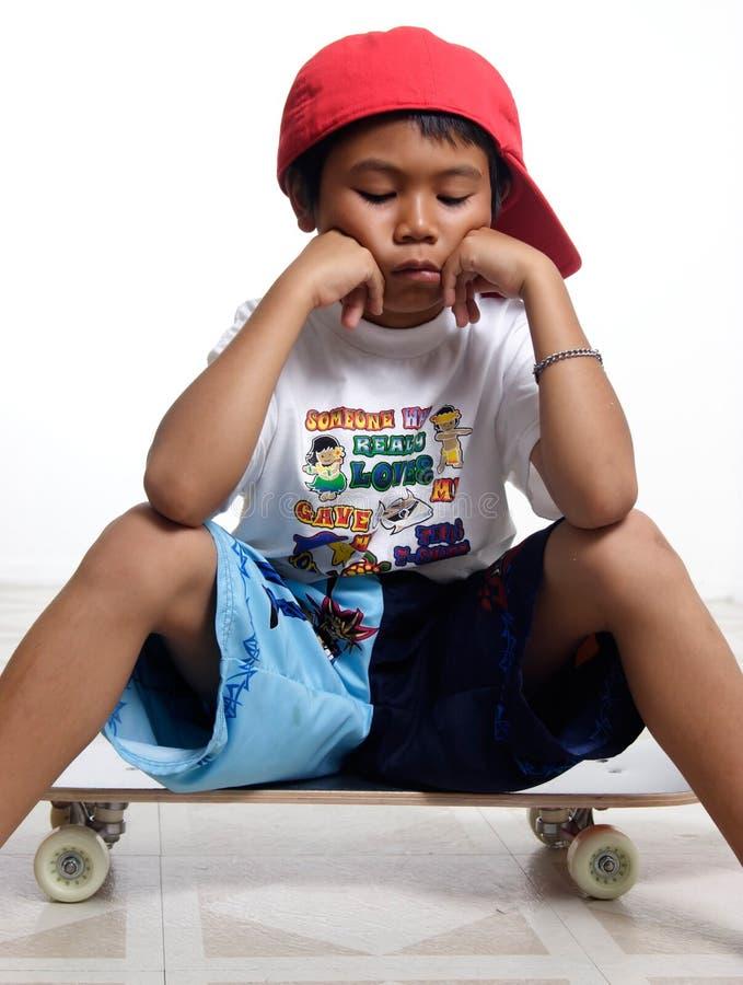Droevig weinig jongenszitting op zijn skateboard stock foto