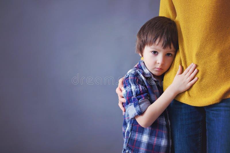 Droevig weinig kind, jongen, die zijn moeder thuis koesteren royalty-vrije stock afbeeldingen