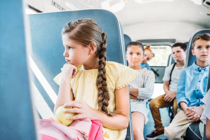 droevig weinig schoolmeisje die op schoolbus berijden stock afbeeldingen