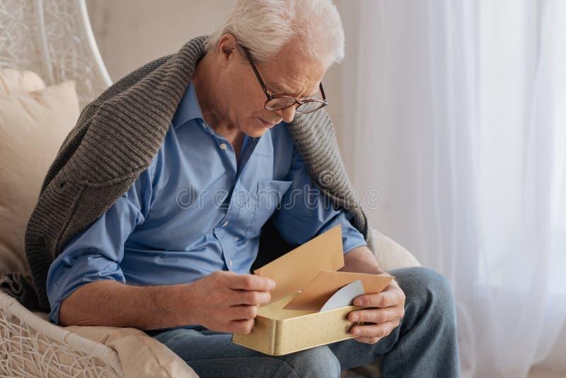 Droevige aardige mens die zijn oude brieven omkeren stock fotografie