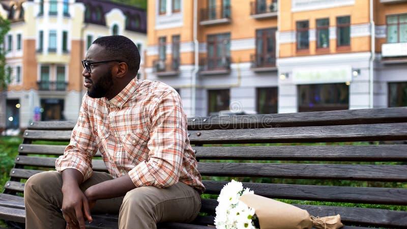 Droevige Afrikaanse mensenzitting eenzaam op stadsbank met bloemboeket, ontbroken datum royalty-vrije stock afbeelding