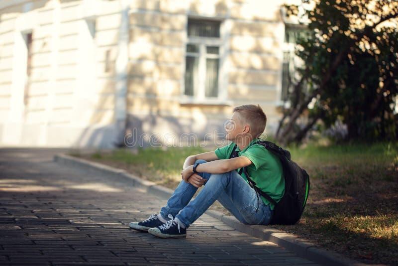 Droevige alleen jongenszitting op weg in het park in openlucht stock afbeeldingen
