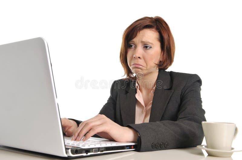 Droevige bedrijfs rode haired vrouw in spanning op het werk met computer stock fotografie