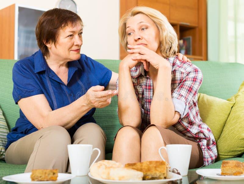 Droevige bejaarden die problemen bespreken stock foto