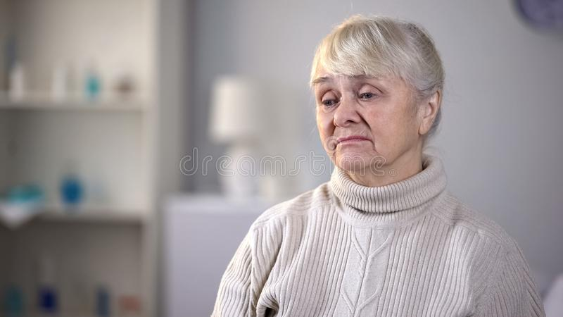 Droevige bejaardezitting alleen in woonkamer, die over gezondheidsproblemen denken stock foto