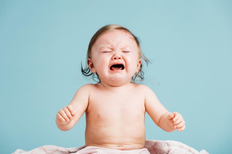 Droevige beneden en babyzitting die schreeuwen stock fotografie