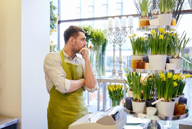 Droevige bloemistmens of verkoper bij de teller van de bloemwinkel stock afbeelding