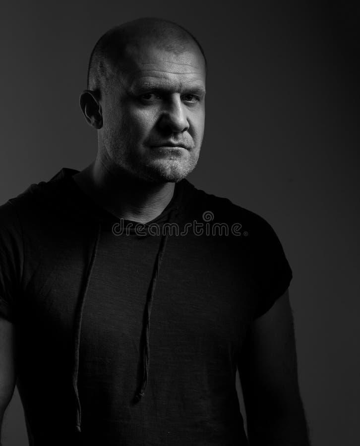 Droevige boze misdaadmens met kale hoofd het kijken geheimzinnigheid en agressief in zwart overhemd op donkere grijze achtergrond royalty-vrije stock fotografie