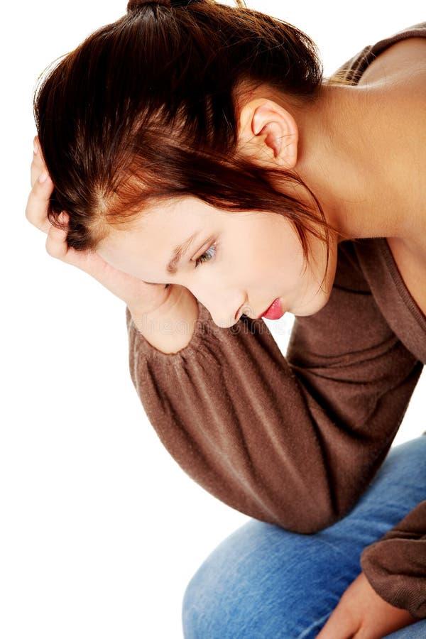 Droevige brunette die en wat betreft haar hoofd denkt. stock foto