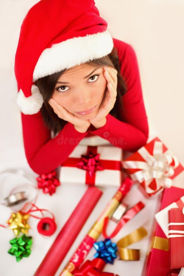 Droevige de vrouwen verpakkende giften van Kerstmissanta stock foto