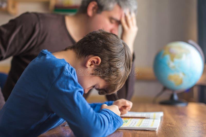 Droevige die vader over zonenmislukking wordt vermoeid op wiskundethuiswerk stock foto