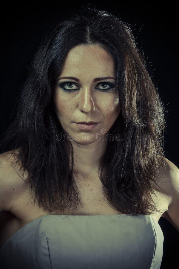Droevige donkerbruine vrouw met lange haar en avondtoga stock foto's
