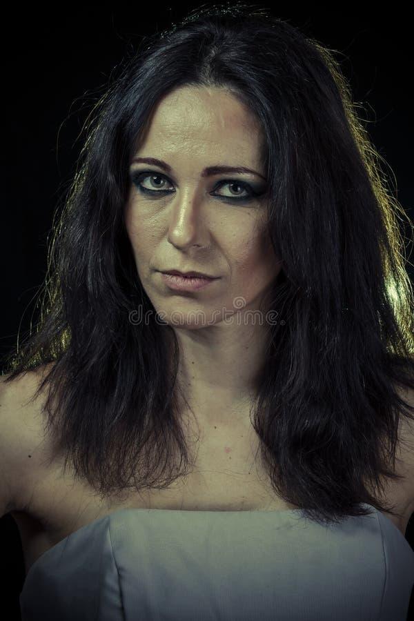 Droevige donkerbruine vrouw met lange haar en avondtoga stock afbeeldingen