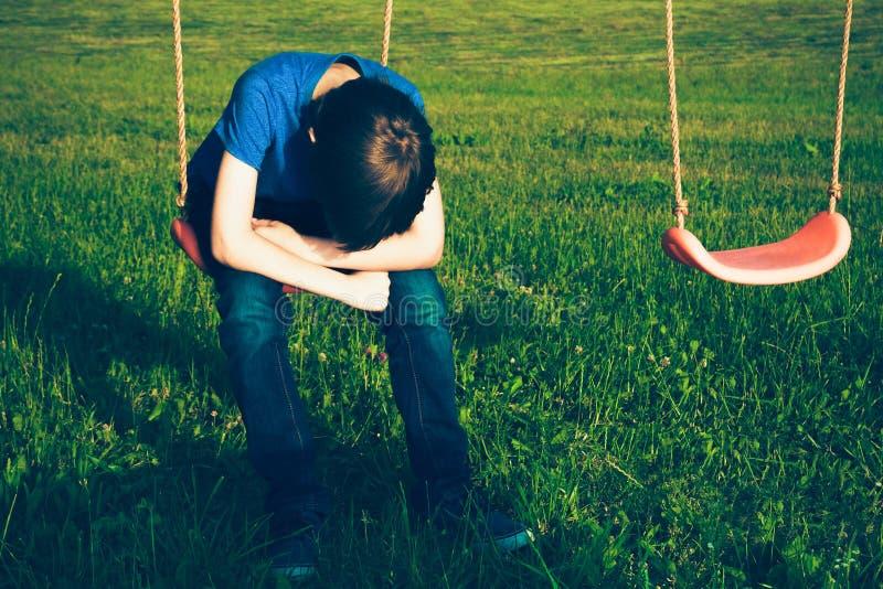 Droevige eenzame jongenszitting op schommeling royalty-vrije stock foto's