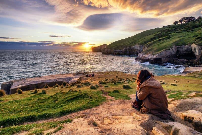 Droevige eenzame meisjeszitting op rots het letten op zonsondergang stock fotografie